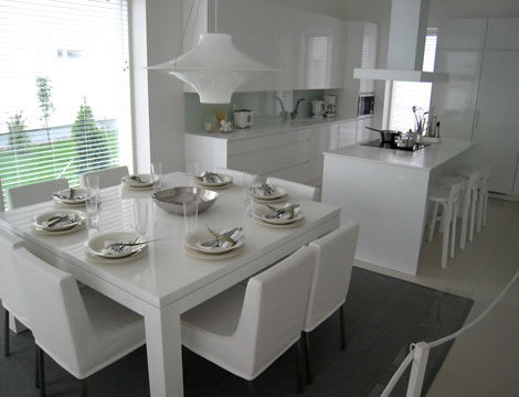 Contemporary-kitchen-with-dining-room-with-gray-carpet-white-handing-lamps-and-white-table-and-chairs