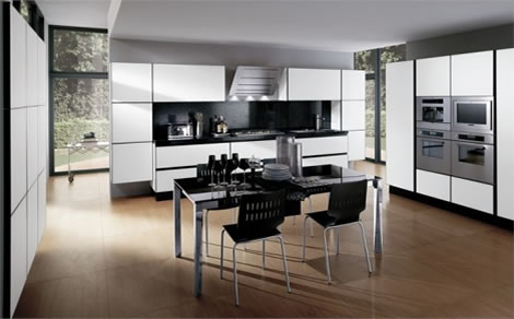 Modern-kitchen-in-black-and-white-with-beige-wood-floor-white-drawers-and-black-chairs-and-table